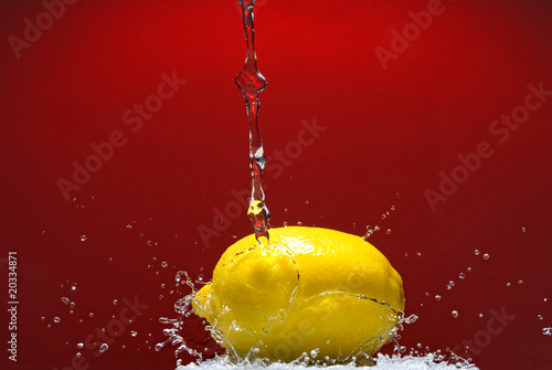 Fresh lemon and water splash on red