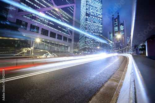 Tuinposter China Fast moving cars lights blurred over modern city background