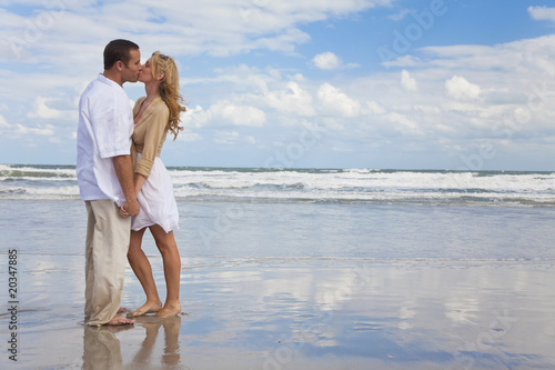Man and Woman Couple Holding Hands Kissing On A Beach