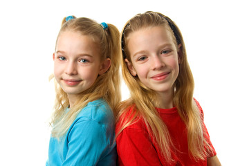 Two young girls looking in camera over white background