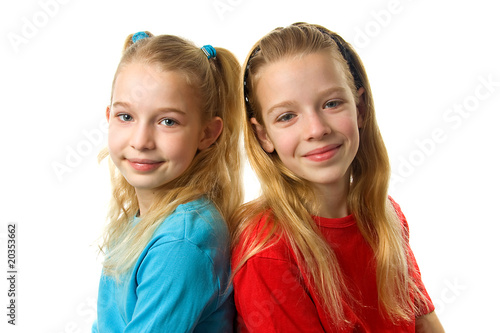 Leinwanddruck Bild Two young girls looking in camera over white background