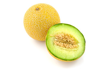 Whole and half yellow melon over white background