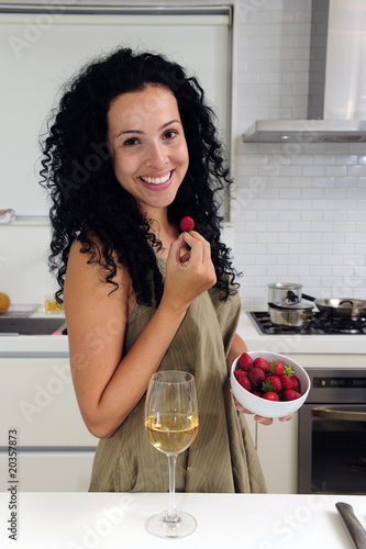 Woman eating strawberries and drinking wine