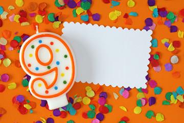 Number nine birthday candle on orange background