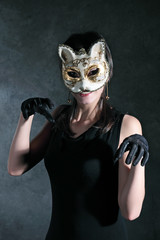 Girl in the Venetian mask of a cat against a dark background