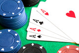 Four aces and poker stacked chips