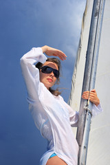 The girl stand on a yacht nose keeping for a sail during a storm