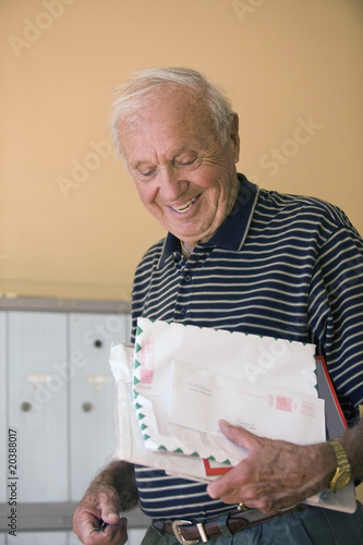 Senior man smiling with his mail