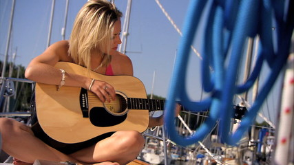 Beautiful young girl with guitar aboard yacht