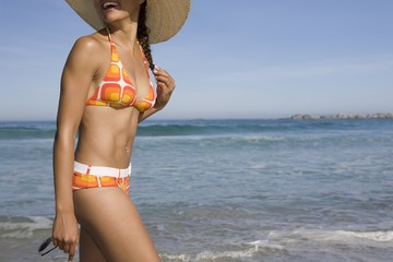 Young woman in sunhat and retro swimwear walking on beach