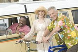 Senior couple stand with bikes next to campervan driven by mature man