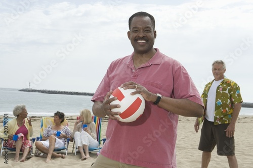 Mature man stands with volleyball on beach, friends grouped behind