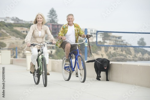 Senior couple cycle with dog on promenade