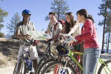 group of friends stand with mountain bikes looking at map