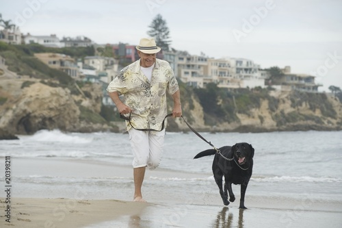 Senior man exercising dog on beach