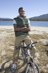 Man stands with mountain bike and arms folded