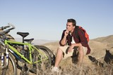 Man sits on rock thinking with mountain bikes