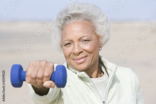 Senior woman excercising with dumbbell on beach