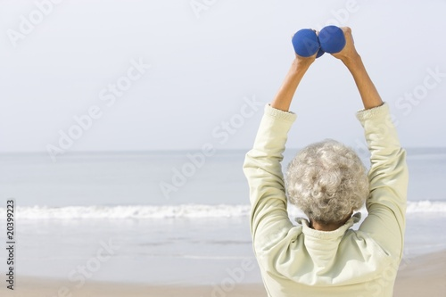 Senior woman excercising with dumbbells on beach