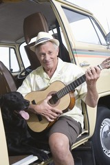 Senior man sits in his campervan with a guitar and his pet dog