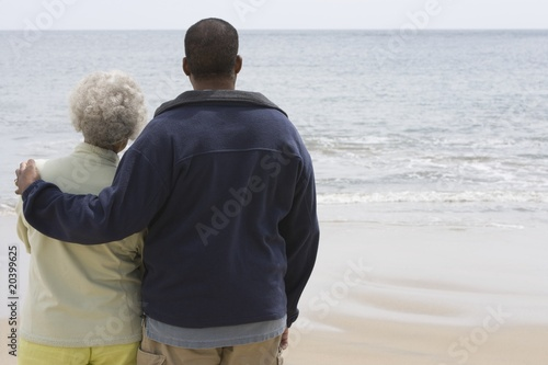 Man stands with his arm round a woman at waters edge