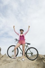 Mid adult woman stands with mountain bike and arms raised