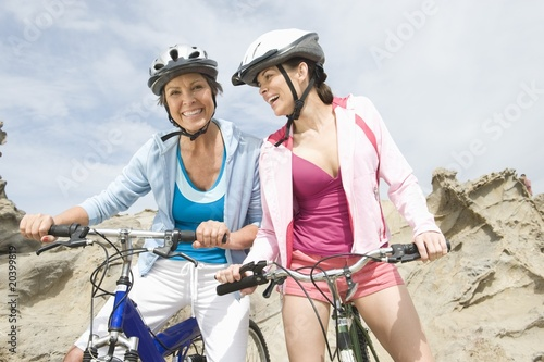 Mature and mid adult women stand with bikes