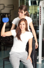 Young woman and instructor in the gym