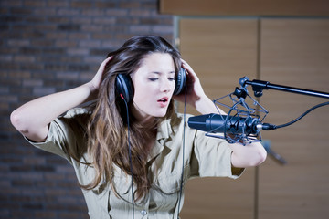 Young beautiful retro woman recording the sound in professional