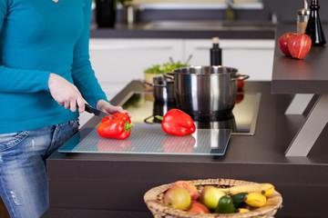 junge frau schneidet paprika in der küche