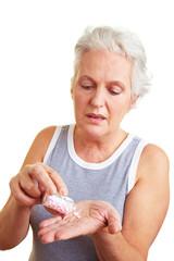 Seniorin nimmt Pillen auf die Hand