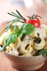 Tortellini with cheese sauce and arugula