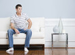 Man Sitting on Living Room Couch