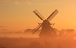 Dutch windmill in autumn fog during sunrise.