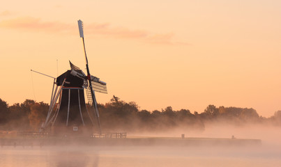 Dutch windmill in autumn fog.