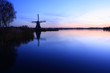 Dutch windmill at a lake during sunset