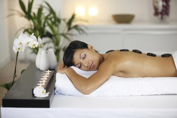 Femme avec des pierres chaudes de massage