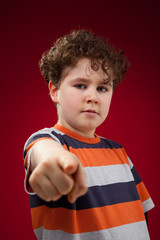 Boy pointing on red background