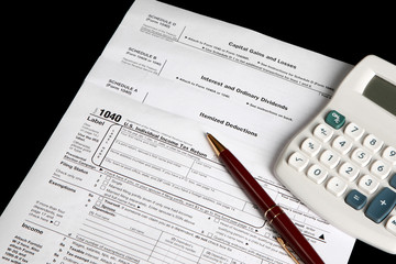 Tax forms on a black background with calculator and pen