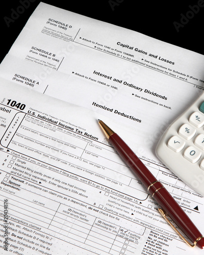 Tax forms on a black background with pen - vertical