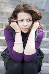 pensive young woman sitting on stairs prop up her chin