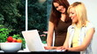 Beautiful blonde & brunette girls use a laptop computer at home