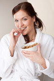 Woman in bathrobe holding bowl with cereals for breakfast poster