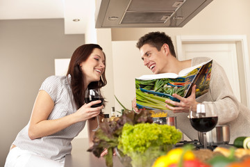 Young couple in kitchen choosing recipe from cookbook