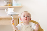 Baby boy in high chair holding fork and spoon