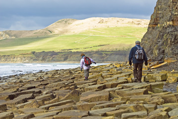 A senior couple taking a walk along a rocky coastline