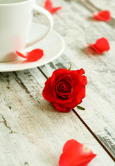 red rose and cup on old wooden