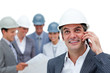 Confident male architect on phone in front of his team