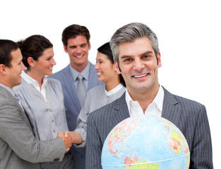 Mature manager holding a terrestrial globe in front of his team