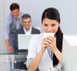 Brunette woman drinking coffee in the office
